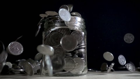 Slow motion, a pile of coins falls into an empty glass jar on a black background. Ukrainian coins fall into a jar.