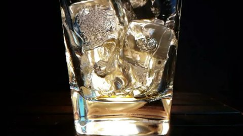 barman pouring whiskey in the glass with ice cubes on wood table and black dark background, focus on ice cubes, whisky relax time on warm atmosphere