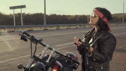 The old biker grandmother in a leather jacket and in a red bandana puts on leather gloves without fingers. An elderly woman stands near a steep motorcycle, against a background of nature, an empty
