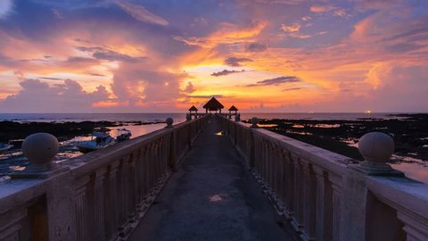 Timelapse of beautiful and colourful sunrise over a concrete jetty in the morning at Tanjung Balau, Johor, Malaysia