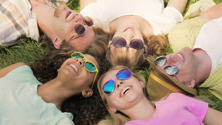 Happy friends in sunglasses lying grass, talking and laughing, sharing secrets #1015343689