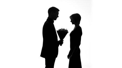 Boyfriend giving flowers girlfriend, happy couple shadow kissing, romantic date
