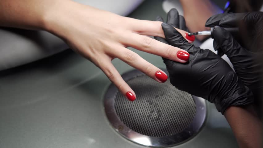 Woman having a nail manicure in a beauty salon with a closeup view of a beautician applying varnish with an applicator. Master painted nails with nail polish. Details shot of hands applying red nail.   Shutterstock HD Video #1015358689