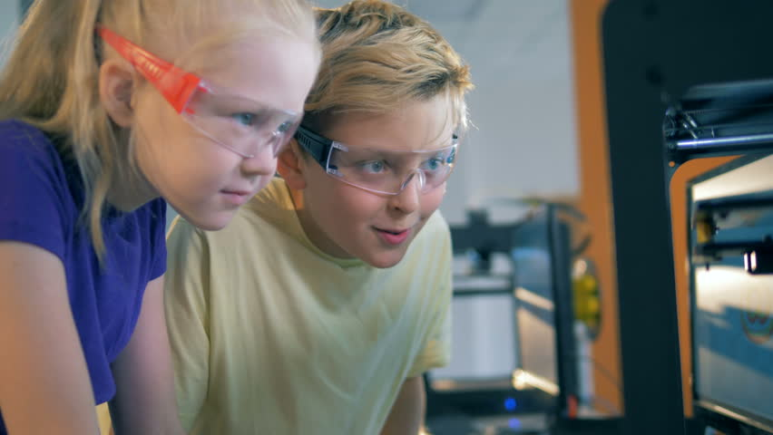 Quantorium facility with an 3D printer held in it and two kids watching it at work | Shutterstock HD Video #1015364569
