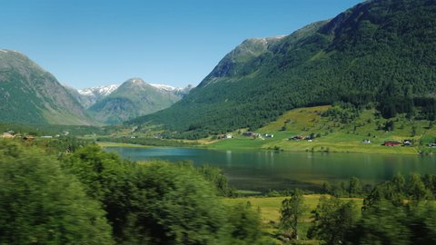 A picturesque Norwegian fjord, on the banks along the water, traditional wooden houses. Idyllic landscape, view from the window of a traveling car