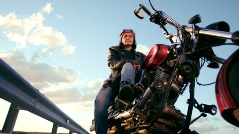An elderly woman in a bandana, leather jacket and gloves is sitting on a cool motorcycle and smiling. Looks down and shows a gesture of rockers. Happy retirement life after retirement.