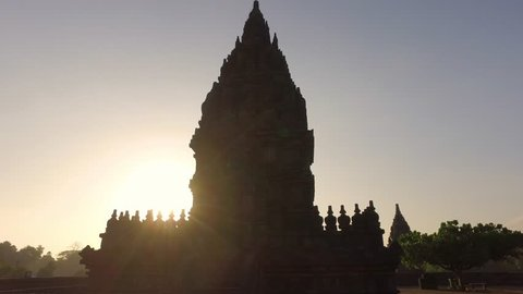 Cinematic silhoutte truck slide shot of Prambanan Temple revealing sun rising behind the temple and the trees