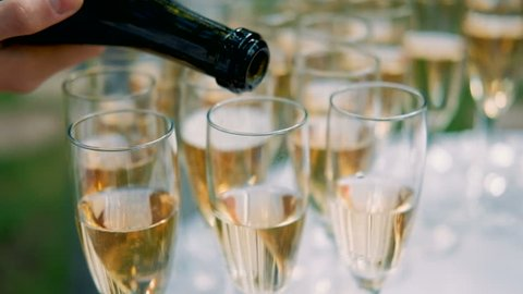 waiter pours champagne on glasses on wedding