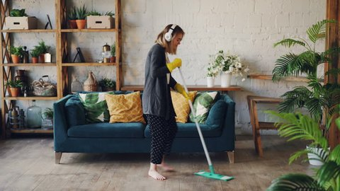 Attractive girl in headphones is listening to music and dancing wih mop during domestic work, she is mopping floor at home and having fun. Women, joy and houses concept.