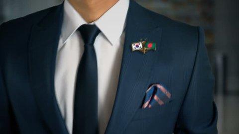 Businessman Walking Towards Camera With Friend Country Flags Pin South Korea - Bangladesh