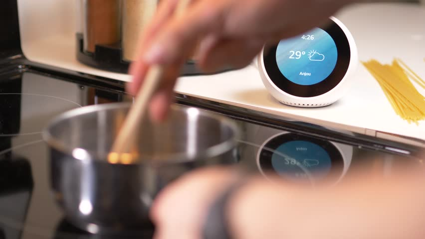 MONTREAL, CANADA - August 2018 : Cooking while making a shopping list on a smart home assistant device.