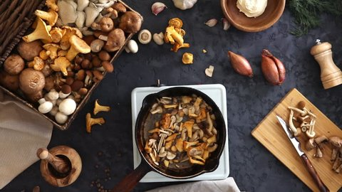 Top view of preparation and frying of edible wild mushrooms. Mix of chanterelle, portobello, shiitake in Cast-iron pan. Cooking with spices, butter, parsley, onion, leek, garlic.