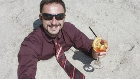 Man Buried in Beach Sand Drinking a Cocktail Overhead View