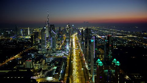 Dubai - March 2018: Aerial city view of night illuminated Sheikh Zayed road skyline skyscrapers commercial condominiums suburbs vehicle transport highway metro UAE RED WEAPON