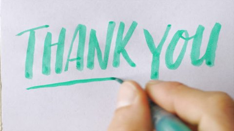 Hand writing the words THANK YOU in block letters with a green brush pen