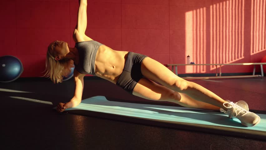Woman doing a Side plank for abdominal workout on blue mat. This Video about fitness. Sunset light.
