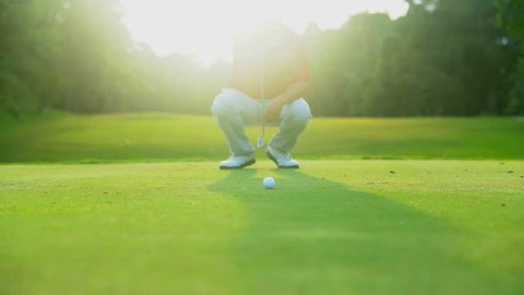 Golf sport concept, Golfer check direction to putting golf ball to hole in open tournament on hills in golf course on over light sun of sunset. Focus ball to focus hole shot.