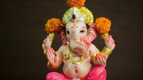 Hindu God Ganesha. Ganesha Idol with marigold flower. Slider shot.