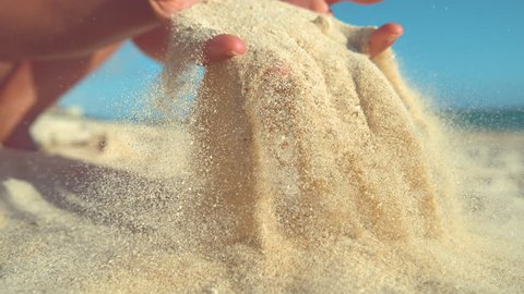 SLOW MOTION, CLOSE UP: Unknown playful young woman throws a handful of white sand over the camera. Carefree girl on summer holiday in Cook Islands plays on stunning tropical beach with soft sand.