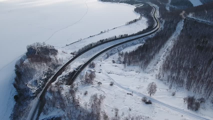 Winter Aerial drone follow Trans-Siberian railway cargo container long trains near frozen Baikal lake. Cinematic professional 4k footage. Cold snow Siberia Russia best journey.