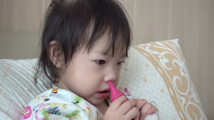 Baby girl using baby nasal aspirator, She is doing a mucus suction.