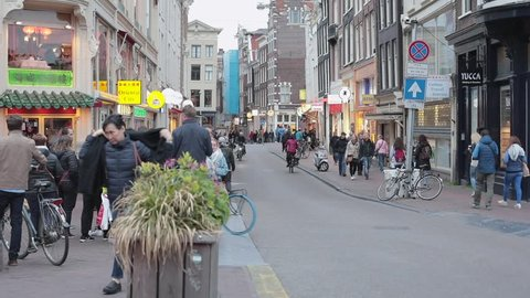 Amsterdam, Netherlands - May 18, 2018: Crowd of Cyclists and Tourists in Front of Coffeeshop in the Red Light District in Amsterdam, Netherlands.