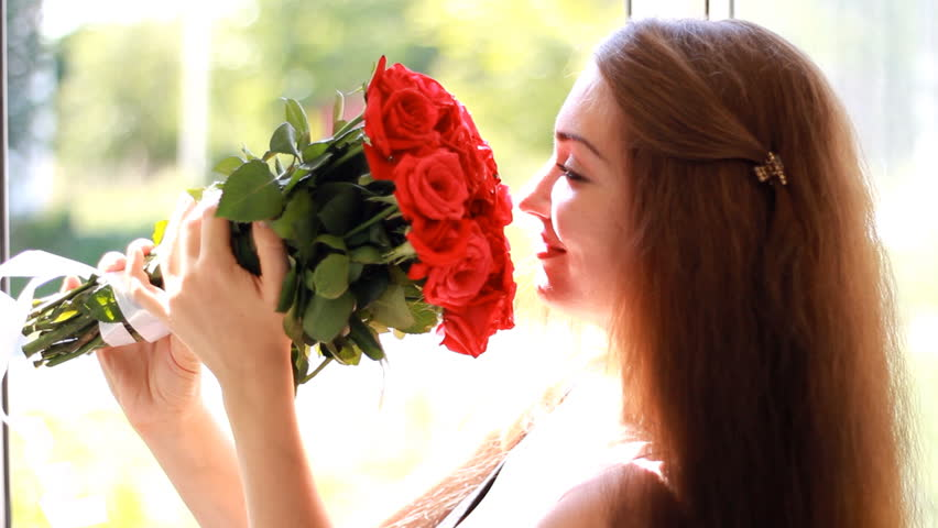Young woman with a bouquet of red roses near an open window. A beautiful girl enjoys the aroma of flowers #1015563169
