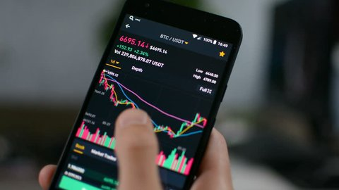 Businessman is checking Bitcoin price chart on digital exchange on mobile phone screen, cryptocurrency future price action prediction concept