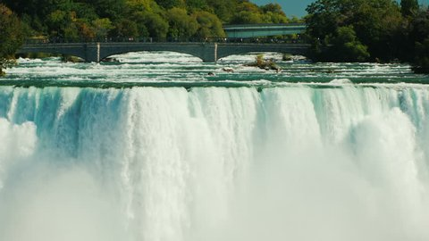The powerful water flow of Niagara Falls and the bridge over the Niagara River