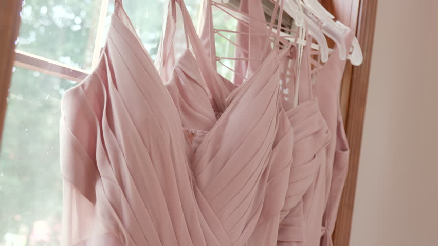 Bride Bridesmaids Dresses Hanging in Front of Window Before Ceremony