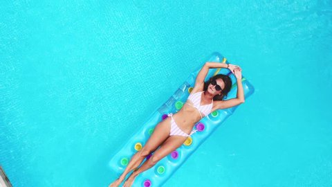 AERIAL. Top view. Camera zooming out. Outdoor lifestyle portrait of young pretty sexy girl posing with neon bright swimming mattress at the pool in luxury villa at the jungle, wearing bikini and
