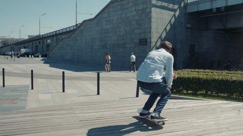 Skater skateboarding skateboarder making 360 flip trick from 4 stairs slow motion kickflip ollie from gap on street bridge.