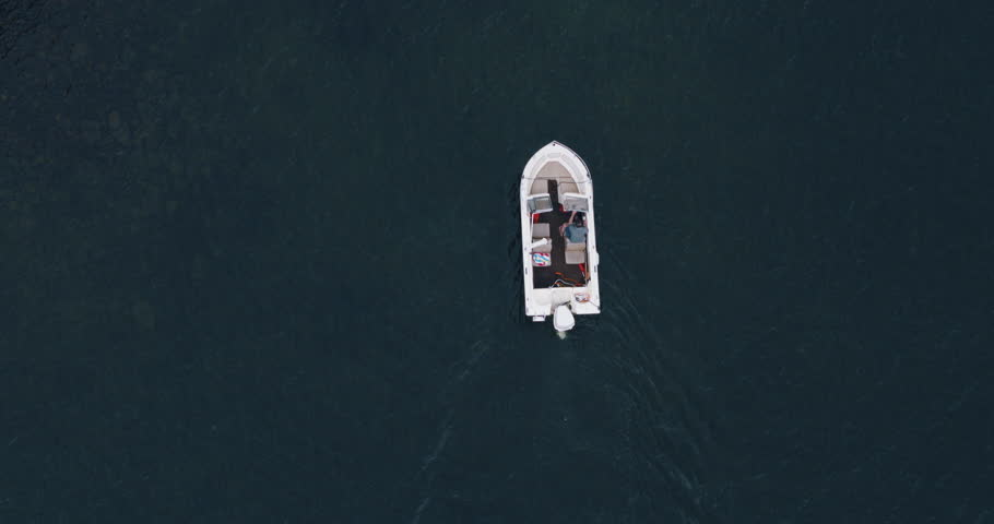 Overhead shot of young man docking outboard motor boat at wooden dock on lake
