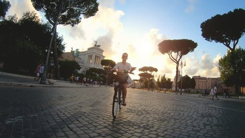 Young woman riding a bike in Rome at sunset. Beautiful elegant white dress and skirt. Camera dolly shot.