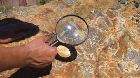 Geologist hand examines rock crystals mineral under magnifying glass. A large block of rock with inclusions of minerals lies in the mine dump. Study of mineral composition of minerals in ore: geology