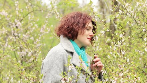 Pretty romantic young red head woman with cherry branches blossom in spring park. Spring trees background. Portrait close up.