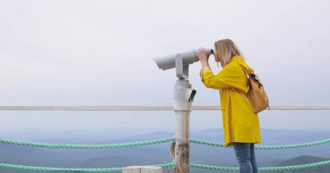 Woman in yellow raincoat looking through tourist binoculars at the mountains