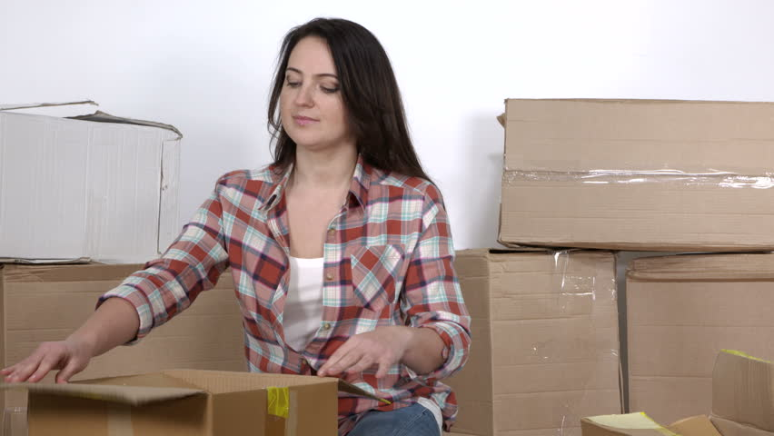 Woman on the floor in a new apartment unpacks the moving cardboard boxes | Shutterstock HD Video #1015678279