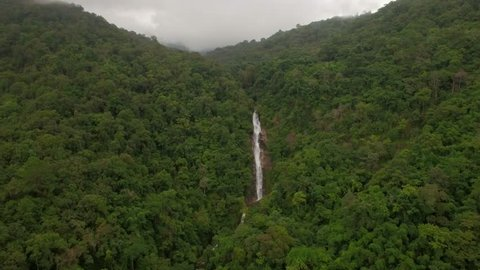 Dramatic aerial drone shot of the waterfall in a deep forest in Thailand