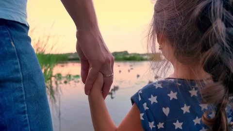 Father is standing with his small daughter near lake and watch ducks, holds her hand, sunset, family concept
