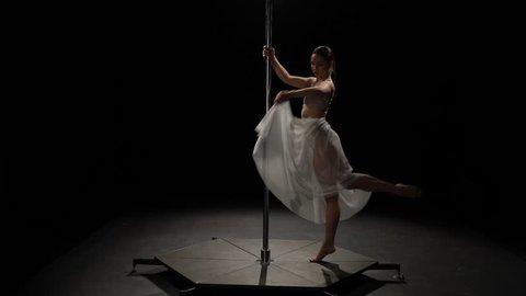 Female dancer performs sexy poledance . Black background