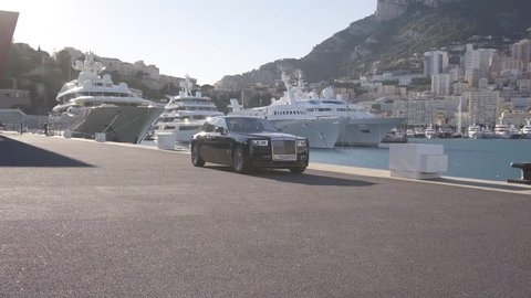 Monte - Carlo, Monaco 28 August 2018 Rolls - Royce Phantom VIII 8 driving in port with city and Yachts at background.