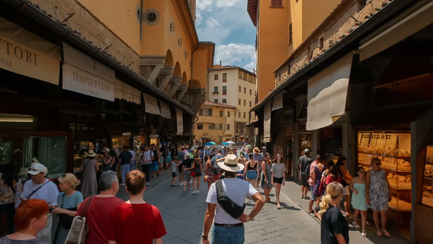 FLORENCE, circa 2018 - POV shot along the Ponte Vecchio bridge in Florence, Tuscany, Italy, known for its traditional goldsmith shops. Florence is considered the birthplace of the Renaissance