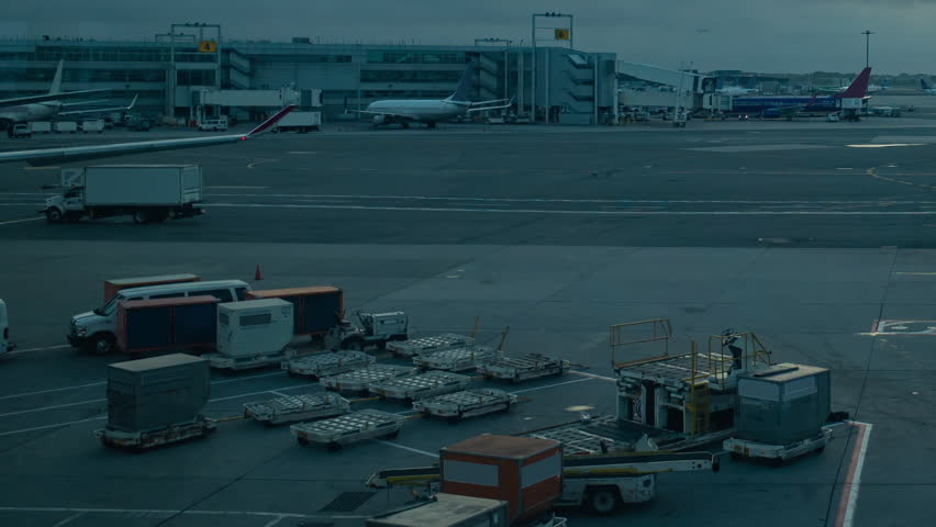 Timelapse of airport runway and terminal at sunrise with planes taxiing and landing, with moving vehicles and lots of activity  JFK airport New York