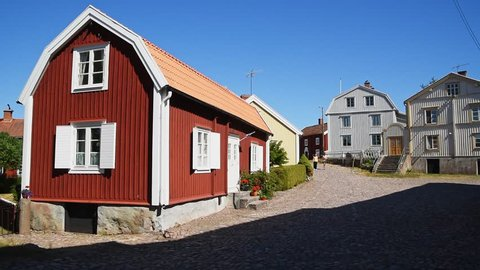 Pataholm, Sweden – June 28, 2018: Vintage cobblestone village street with tourists walking and car passing on an ordinary sunny summer day.