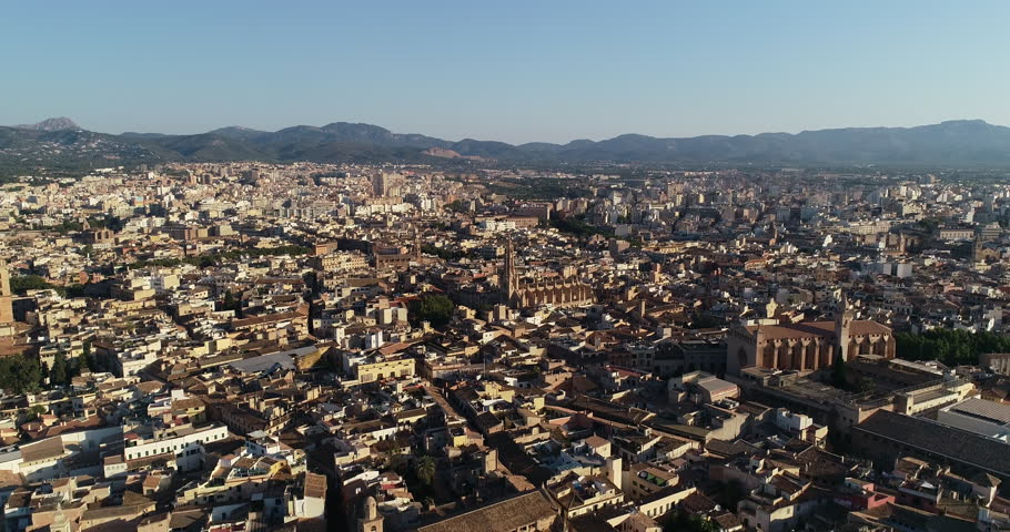 Aerial Drone of Old Spanish Sea side Town In Palma, Houses and Church Stone Buildings with Mountain and Coast Background at Summer City Tourist Holiday Resort in Spain.