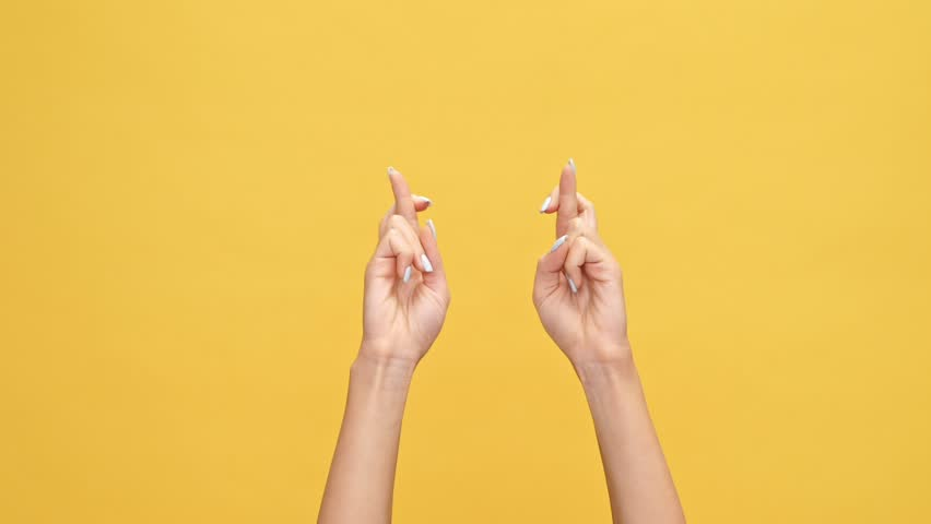 Woman hands praying with crossed fingers and rejoice after that over yellow background