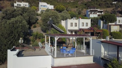 Coastal white houses built uphill facing small bay. Summer villas and beach houses of Bodrum, Turkey. Architecture of residential holiday houses of Bodrum Resort Town in Turkey