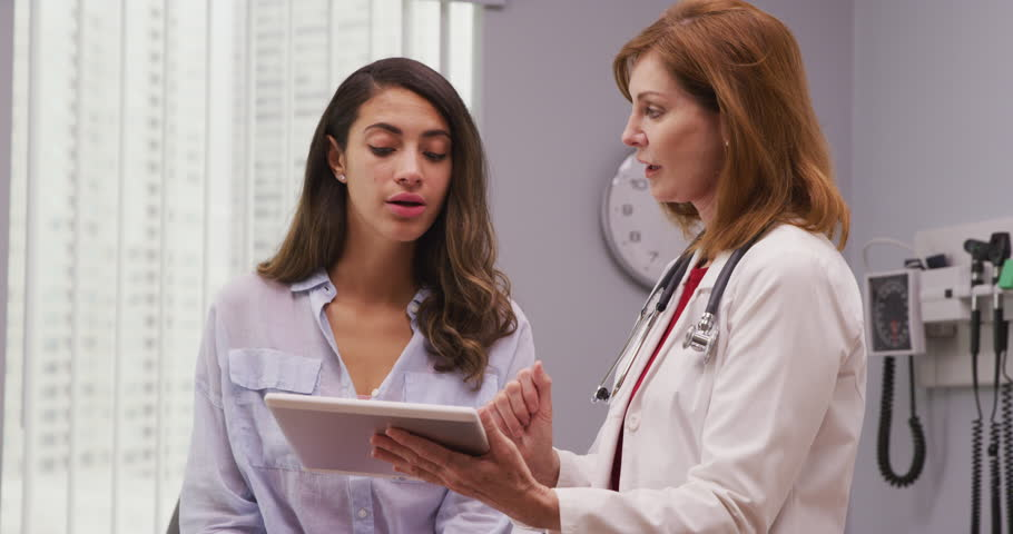 Portrait of lovely young hispanic woman meeting with senior doctor about pregnancy results. Close up of mid aged caucasian doctor using portable tablet to review health history with latina patient