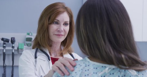 Happy doctor telling patient to be positive after having accident. Positive senior doctor smiling at young patient and placing her hand on her shoulder